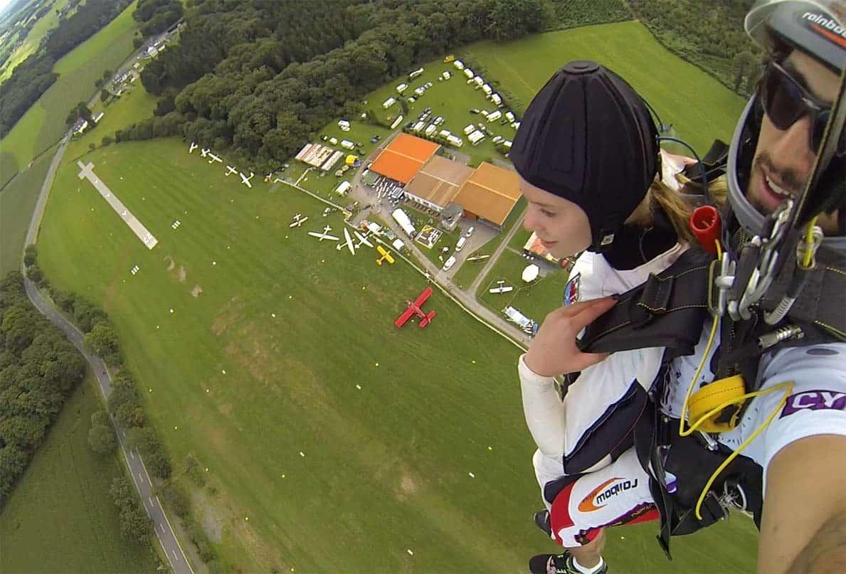 Am Fallschirm hängend. Das Gespann Pilot und Passagier, vorn