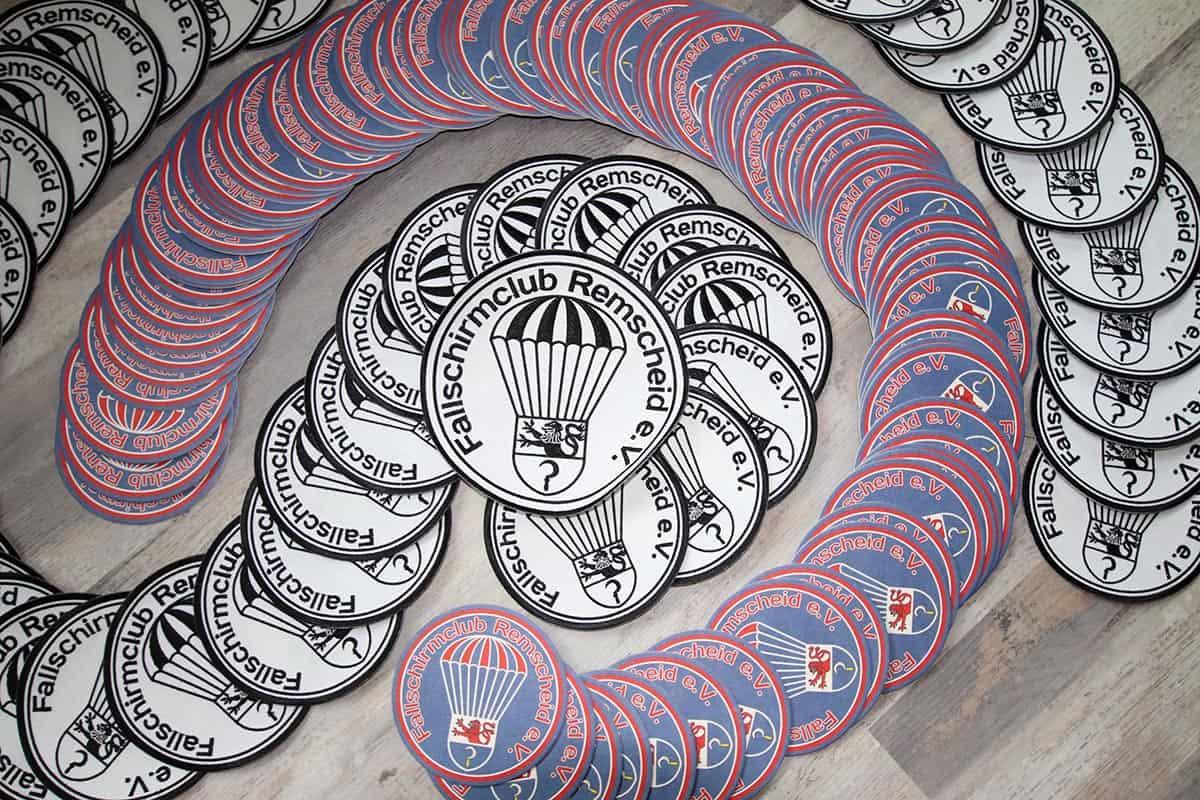 Aufnäher im klassischen schwarz-weiß und in der farbigen Version die Bierdeckel für Veranstaltungen am Boden